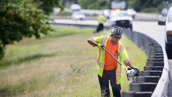 Delaware Department of Transportation worker Janna Perry picks up trash along I-495.
