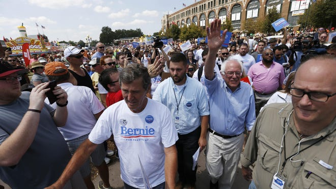 Democratic presidential candidate Bernie Sanders waves to the crowd gathered outside The Des Moines Register Political Soapbox stage Saturday at the Iowa State Fair in Des Moines.
