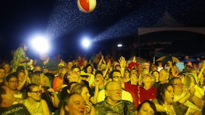 Fans passed around a beach ball in the rain while the Beach Boys performed at the Capitol City Amphitheater at Cascades Park.