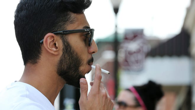 Missouri State University student Mo Ibrahim smokes in downtown Springfield on Thursday. One of three tobacco tax proposals would fund scholarships for higher education.