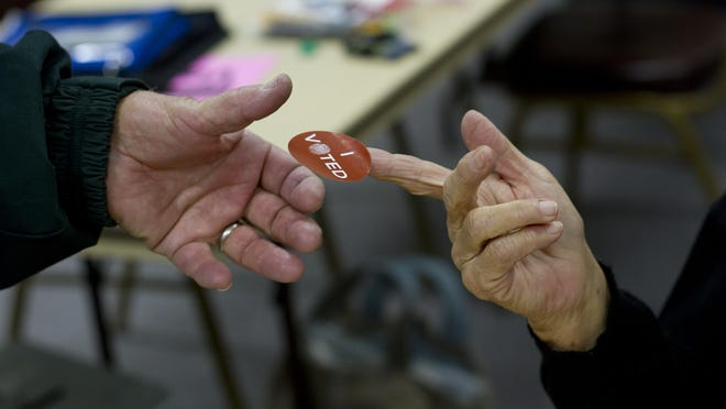 """A voter receives an """"I voted"""" sticker after casting his ballot."""