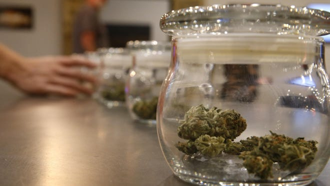 Marijuana for sale is kept in jars for customers to sample smells last month at a new outlet of the Colorado Harvest Co. recreational marijuana stores in Aurora, Colo. While smoking pot in public is illegal in Colorado, one letter writer says that the law doesn't stop people.