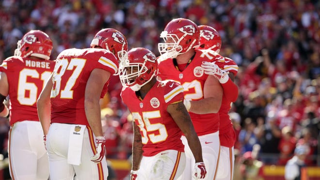 Kansas City Chiefs players Mitch Morse (61), Travis Kelce (87) and Eric Fisher (72) celebrate a touchdown by running back Charcandrick West (35).
