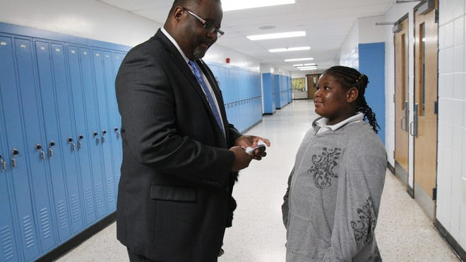 Lamont Repollet, superintendent of Asbury Park School District, looks at 11-year-old Darinnaye Brisco's collection of Bishop Bucks, which are earned by good behavior and can be used to redeem rewards or items at the school store, at Asbury Park Middle School in Asbury Park, NJ Monday November 30, 2015