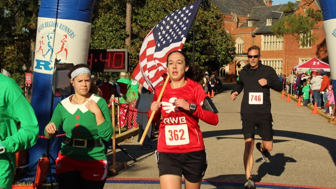 Air Force Maj. Brianne Rahn raced across the Jingle Bell finish line carrying an American flag Saturday morning. She has been carrying the Stars and Stripes with her at each race she enters. Alvin Benn/Special to the Advertiser