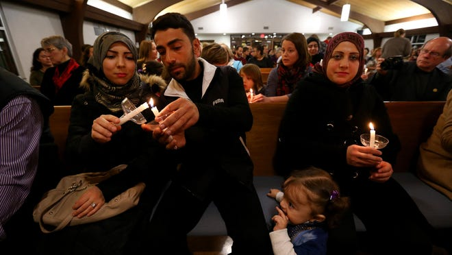 Abdelsattar Assafi (center), who has been in the United States for five days, lights a candle held by his sister Malak Assafi during a rally and candlelight vigil in honor and support of Syrian refugee families. The event was held Friday, Dec. 11, 2015, by the Indiana chapter of the Syrian American Council at Epworth United Methodist Church.