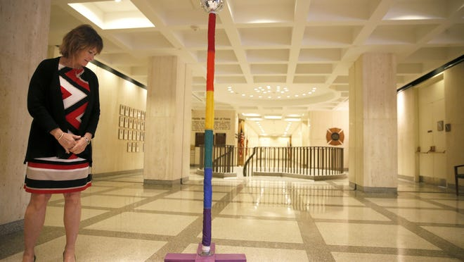 """Pat Kirton inspects the lone public holiday display at the Capitol, a rainbow Festivus pole. """"It's very unique,"""" says Kirton. """"It's festive –¦ though I'm not sure what it means."""""""
