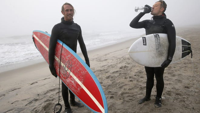 Dylan O'Toole, left, and Michael Reinhardt shown after surfing in the Atlantic Ocean off Rockaway Beach on Christmas Day.