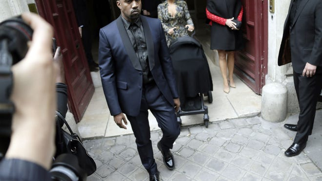 Kim Kardashian (C) pushes a stroller next to her partner Kanye West (L) and her mother Kris Jenner (back-R) as they leave their hotel on May 23, 2014 in Paris. Hip hop star Kanye West and reality TV celebrity Kim Kardashian are expected to tie the knot this weekend, fuelling speculation about the wedding's location. AFP PHOTO/KENZO TRIBOUILLARDKENZO TRIBOUILLARD/AFP/Getty Images ORIG FILE ID: 530064836