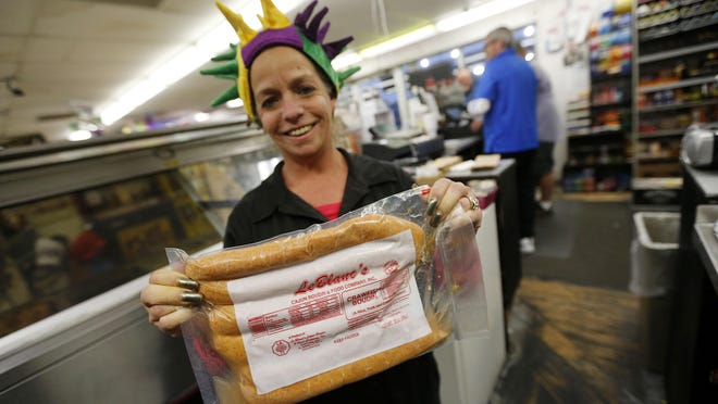 Jeanne Marie Sewell holds a package of Le Blanc's Boudin at the Sav N' Time convenience store and gas station in Harahan, La., Tuesday, Jan. 26, 2016. Boudin is a tradition that dates back to the 1700s, when French Canadians came to Louisiana. Robert Carriker, a professor of history at the University of Louisiana in Lafayette, says Cajuns started using local ingredients and spices to make sausages that are different from Old World recipes.
