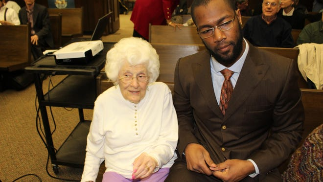 Mallieve Breeding, 94, sits next to Cincinnati Bengal defensive end Michael Johnson at a city council meeting about the Selma-Dallas County YMCA.