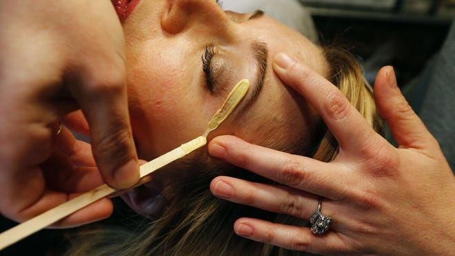 Skin care specialist Lauren Sforza waxes the eyebrows of a client.