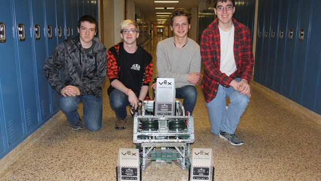 Photo caption: Eric Toepper, Connor Noble, William Levchuk and Dan Fletcher show off their robot and trophies. provided photo