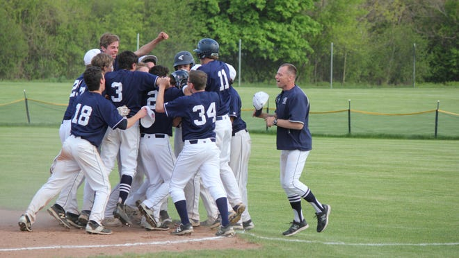 Bloomfield Hills Cranbrook players mob Jordyn Finney (obscured, center) after he singles home the winning run in the Cranes' 4-3 victory over Auburn Hills Avondale.