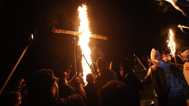 """Members of the Ku Klux Klan participate in cross burnings after a """"white pride"""" rally April 23 in rural Paulding County near Cedar Town, Ga. In 2016, KKK leaders say they feel that U.S. politics are going their way, as a nationalist, us-against-them mentality deepens across the nation."""