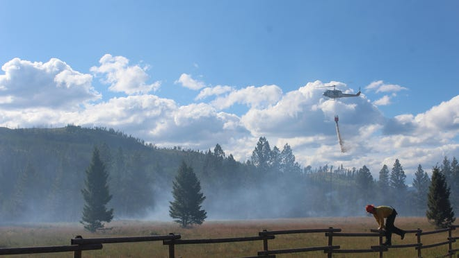 A U.S. Forest Service helicopter drops water on the Elk Trail Loop fire northeast of Lincoln Monday afternoon.