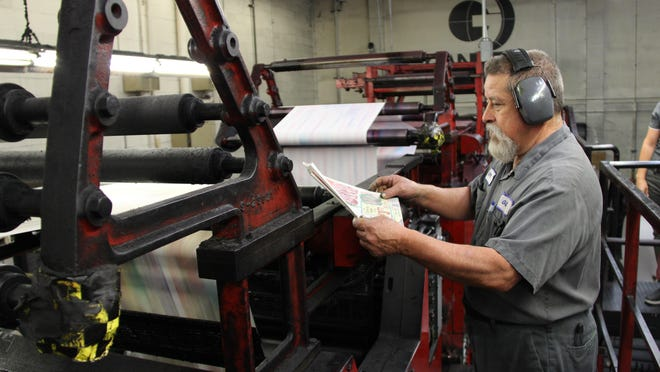 Gil Rios, press operator, looks over an advertisement printed by the Visalia Times-Delta printing press.