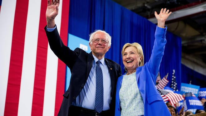 Democratic presidential candidate Hillary Clinton and Sen. Bernie Sanders, I-Vt. wave to supporters during a rally in Portsmouth, N.H., Tuesday, where Sanders endorsed Clinton for president.