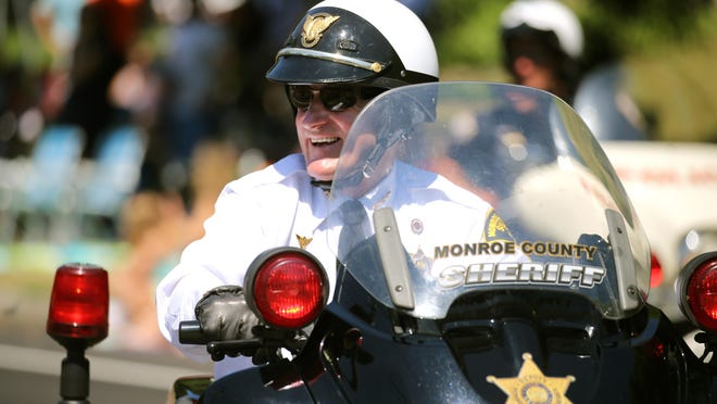 Monroe County Sheriff, Patrick O'Flynn, rides a motorcycle in the Irondequoit July 4th parade.