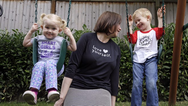 Courtney Hartman, who owns Jessy & Jack, a collection of unisex T-shirts, poses with her children Lois, 2, and Declan, 4, as they wear gender-neutral clothing of Hartman's in Seattle.