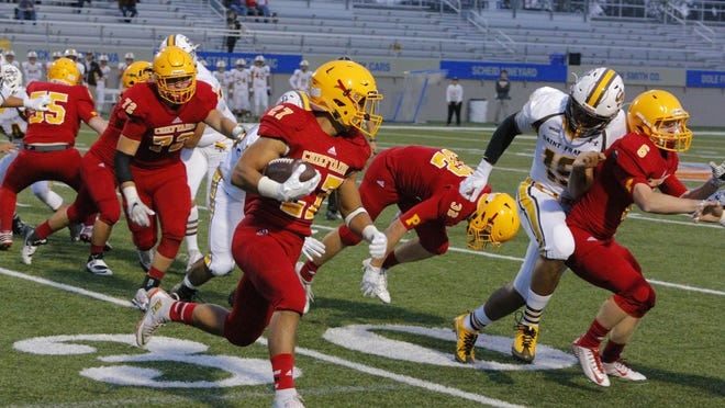 Palma High's Emilio Martinez runs with the ball during the first quarter of Friday's game.