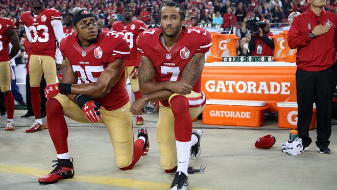 San Francisco 49ers Eric Reid (35) and Colin Kaepernick (7) take a knee during the National Anthem prior to their season opener against the Los Angeles Rams during an NFL football game Monday in Santa Clara, Calif.