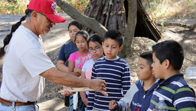 John Sartuche, Wuksachi Tribe member, shows Woodlake students tule reeds at the California Native-American Student Days in Three Rivers, Wednesday.