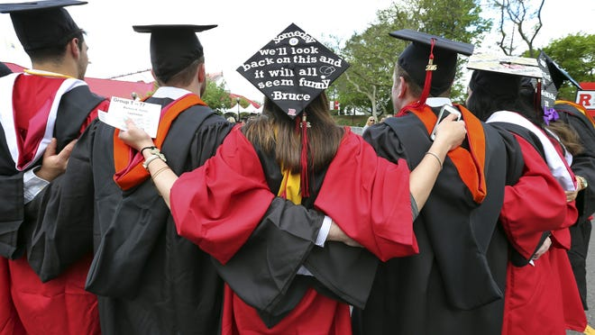 Students embrace as they arrive for Rutgers graduation ceremonies May 15 in Piscataway, N.J. More Americans are getting buried by student debt, burdening economic growth.