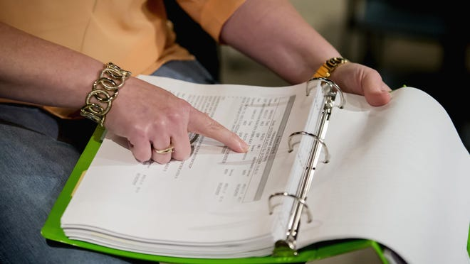 """Deb Roschen goes through notebooks of evidence of how authorities accessed information about her through law enforcement databases, during an interview in Rochester, Minn., on July 11, 2016. The former county commissioner alleged in a 2013 lawsuit that law enforcement and government employees inappropriately ran repeated queries on her and other politicians over 10 years. The searches were in retaliation for questioning county spending and sheriff's programs, she says. """"Now there are people who do not like me that have all my private information ... any information that could be used against me. They could steal my identity, they could sell it to someone,"""" Roschen said. """"The sense of being vulnerable,"""" she added, """"there's no fix to that."""" (AP Photo/Bruce Kluckhohn)"""