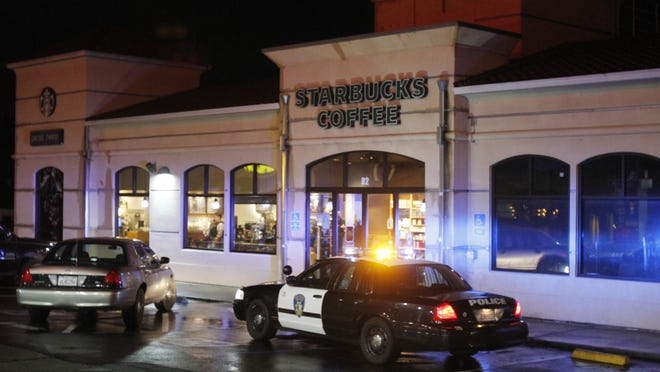 Vallejo Police officers work at the scene of a shooting in Vallejo, Calif., on Sunday, Oct. 16, 2016. Andrew Powell targeted two Northern California police officers who were taking a break at a coffee shop in an ambush that was foiled when his gun malfunctioned, a police chief said Monday. Powell, who was wearing body armor, fled when he could not get his weapon to fire, and the officers gave chase, shooting him three times, authorities said at a news conference. He is in critical but stable condition.