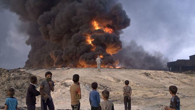 People watch a burning oil well in Qayyarah, about 30 miles south of Mosul, on Sunday.