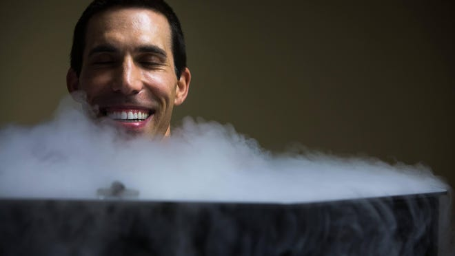 A mist of cool nitrogen floats around Eric Wolf, 44, of Newark as he stands for several minutes inside the cryotherapy chamber.