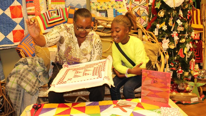 Mary Margaret Pettway, left, shows niece Tanisha Pettway the proper way to start a quilt.