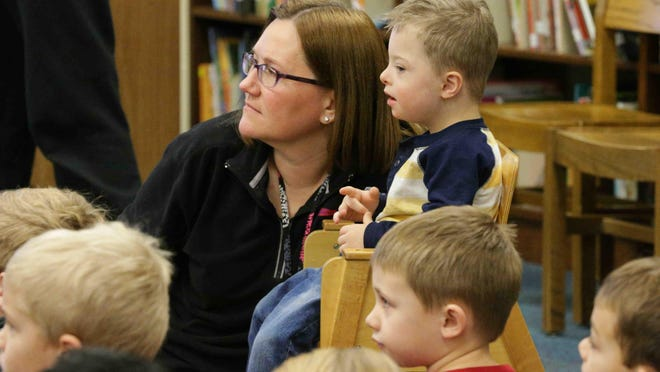 Cumberland Road Elementary School, Preschool Teacher, Missy Knouse, left, and student Mason Wilson, right, watch a puppet show put on by the Joseph Maley Foundation, showcasing children with different abilities, Dec. 5, 2016. The show explained disabilities and abilities of and for young children.