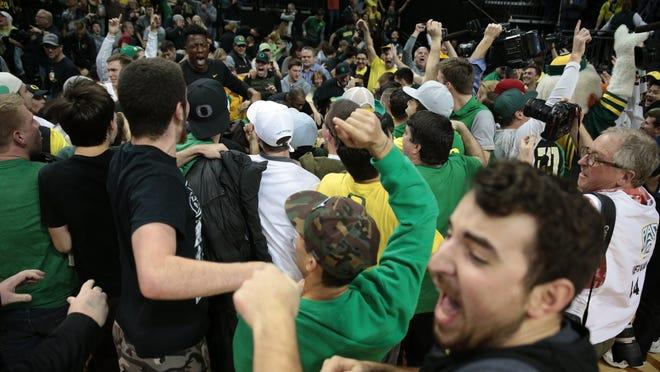 Oregon Ducks fans run onto the basketball court following a win against UCLA Bruins at Matthew Knight Arena.