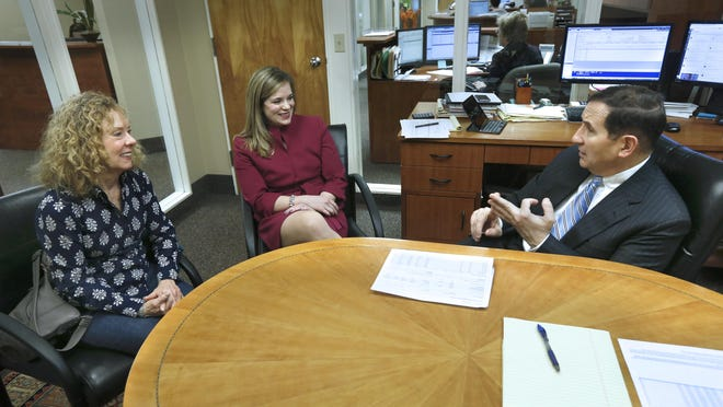 Client Carol Kase and financial adviser Caroline Hill meet with chairman George Conboy at Brighton Securities.