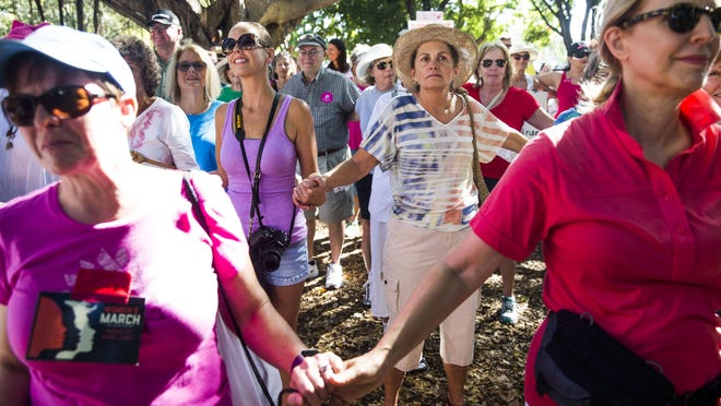 Attendees hold hands in Cambier Park in downtown Naples after the Naples Women's March for Social Justice on Saturday. At least 2,500 people took to the streets for the march.