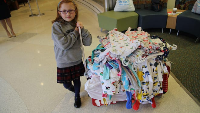 Mary Suggett, 8, of Sparta, with the 150 pairs of pajamas she donated on March 28 to Goryeb Children's Hospital.