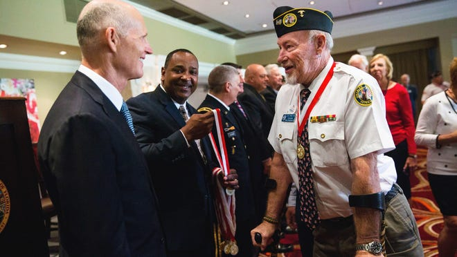 """Vietnam veteran Larry """"Stixxx"""" Tiller, 71, chats with Gov. Rick Scott after receiving the Governor's Veterans Service Award at the Bonita Bay Club on Monday. Scott said: """"We can never fully repay our debt of gratitude to the brave men and women who served and protected our freedoms. The Governor's Veterans Service Award serves as a testament of thanks from Floridians everywhere."""""""