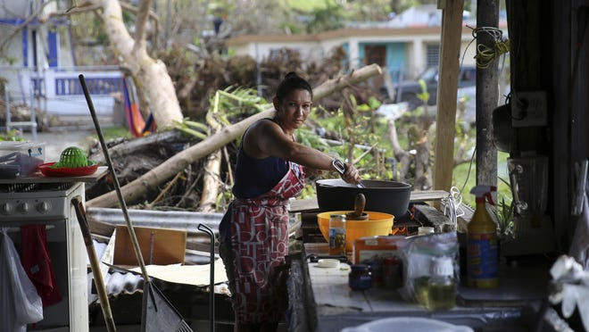 Int this Sept. 29, 2017 photo, Margarita Burgos poses for a portrait while cooking outside over a wood fire, due to the lack of electricity, in the aftermath of Hurricane Maria in Yabucoa, Puerto Rico. Burgos feels her greatest need is clean water, followed by electricity. (AP Photo/Gerald Herbert)