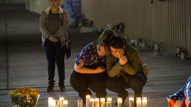 Sara Rivero, right, and her mom, Laura Rodriguez, burn a candle at a memorial site in Las Vegas.