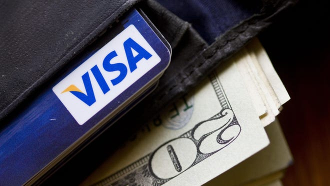 A wallet containing cash and a Visa card is displayed in Surfside, Fla. Reversing fishy charges on your credit card account is easier than you might expect.