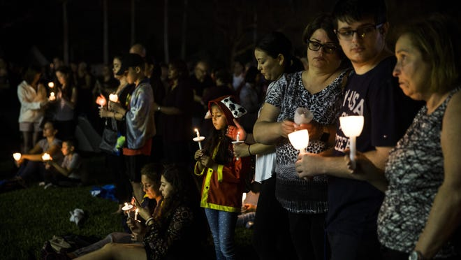 Jasmine Battifora, 6, center, watches her candle flicker during a candlelight vigil at Betti Stradling Park in Coral Springs, Fla. on Monday, Feb. 19, 2018. The Florida PTA organized a statewide candlelight vigil at 7PM to remember and honor the 17 victims of the Marjory Stoneman Douglas High School shooting.