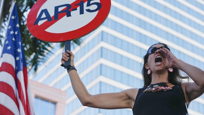 """Alessandra Mondolfi holds a sign against AR-15 weapons as she yells, """"No More"""" during a protest against guns on the steps of the Broward County Federal courthouse in Fort Lauderdale, Fla., on Saturday, Feb. 17, 2018."""