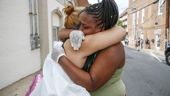 """""""I just don't want to see people get hurt anymore,"""" said Charlottesville resident Mai Shurtleff, left. """"I have a little girl I just can't imagine."""" As Shurtleff sat weeping on the sidewalk near the site where on Saturday a car plowed into a group of counter protesters killing one, Damonia Lee approached. """"We are fighting for equality. I was here. I hugged her. She was so sweet,"""" Lee said, about the young female who lost her life. """"We're going to take our city back. This is a city of love."""""""