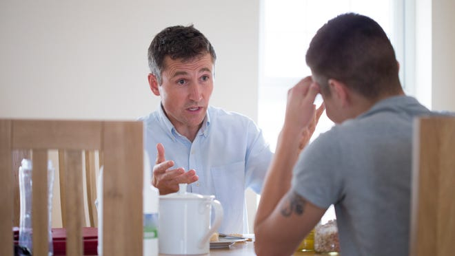 A father and son have a serious conversation sitting at a table at home. Credit: Getty Images.