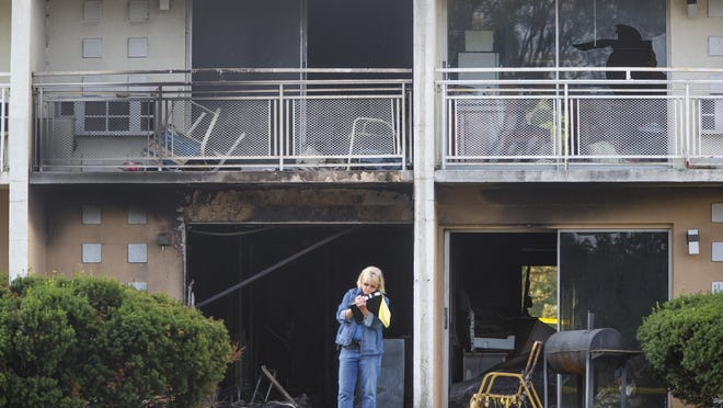 Berrien County Sheriff's Detective Cathy Easton takes notes at the scene of a fire at the Cosmo Extended Stay Motel in Sodus Township, Mich., on Saturday, July 28, 2018. A fire swept through the southwestern Michigan motel early Saturday, killing several members of the same family, including a woman and her children, authorities said.