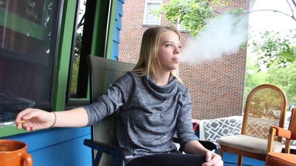 Michigan State University senior Maris Ryckman smokes a cigarette on the porch of her home on Oct. 3. After Michigan State's campus smoking ban went into effect, she waits until she is off-campus before smoking.