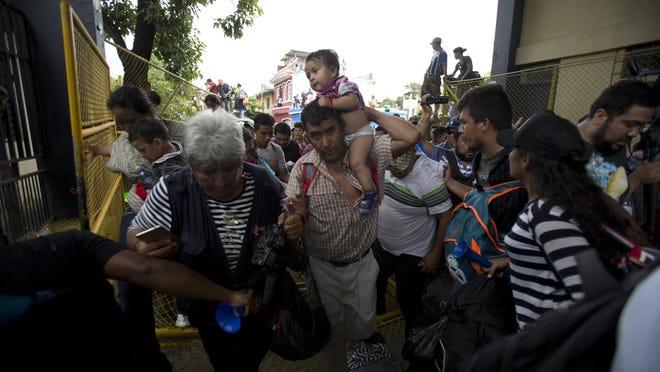 Honduran migrants rush across the border towards Mexico, in Tecun Uman, Guatemala, Friday, Oct. 19, 2018. Migrants broke down the gates at the border crossing and began streaming toward a bridge into Mexico. (AP Photo/Moises Castillo)