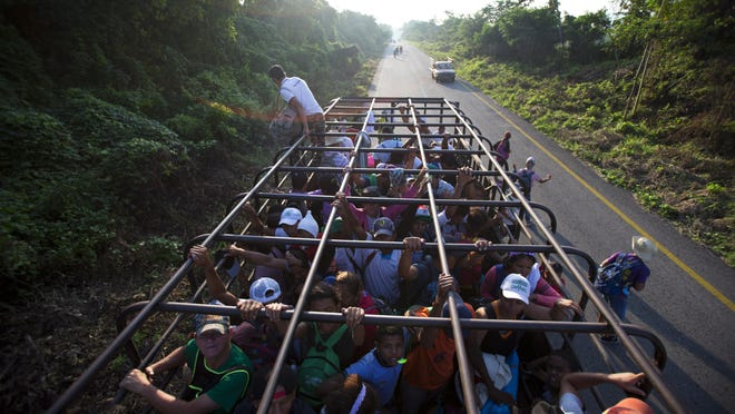 Migrants disembark from a truck in which they had gotten a ride, as a thousands-strong caravan of Central American migrants slowly makes its way toward the U.S. border, between Pijijiapan and Tonala, Mexico, Oct. 25, 2018.